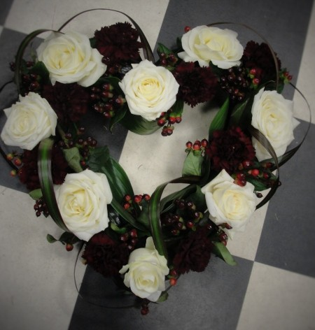 Cream rose & claret carnation heart with dracencia leaf loops